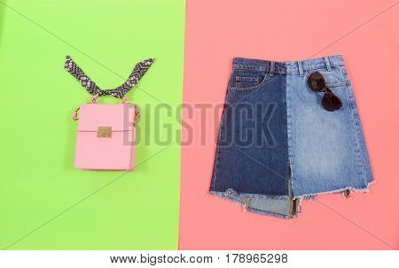 Blue denim skirt with bag isolated on green and pink background