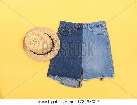 Blue denim skirt and hat isolated and yellow background