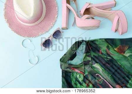 shoes with sunglasses ,hat , Silk blouse green with floral ornament on blue background.