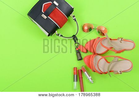 Stylish woman Handbag and cosmetics,makeup accessories on green background