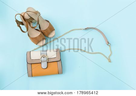 Stylish woman Handbag and shoes on blue background