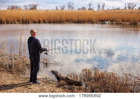 A fisherman with a fishing rod on the river bank.T he concept of a rural getaway.