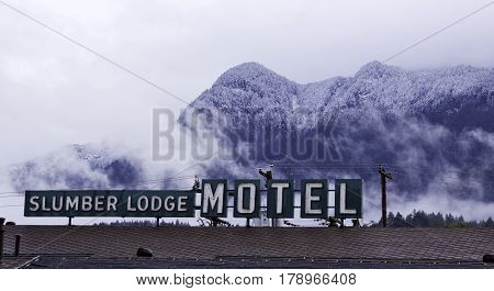 Hope, British Columbia - April 24, 2015 -- Wide view looking at the snow capped Rocky Mountains rising behind the Slumber Lodge Motel sign in Hope, British Columbia on a bright overcast day with haze and clouds in April.