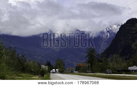 Wide view of the snow capped Rockies along the Trans Canada Highway with cars/trucks and green trees/foliage just outside of Hope, British Columbia on a bright sunny day with blue skies and clouds in April.