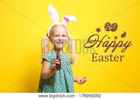 Text HAPPY EASTER and cute little girl with bunny ears holding chocolate rabbit on color background