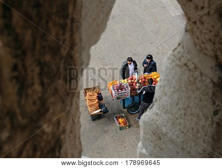 JERUSALEM ISRAEL - MARCH 25 2017: View through a loophole Jaffa Gate of the Old Town to the seller of juices and buyers