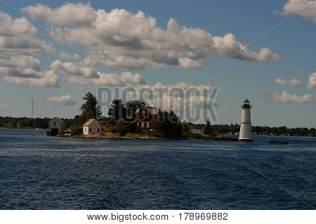 island light house  water  trees  blue sky