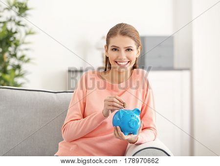 Beautiful young woman putting coins into piggy bank while sitting on sofa at home