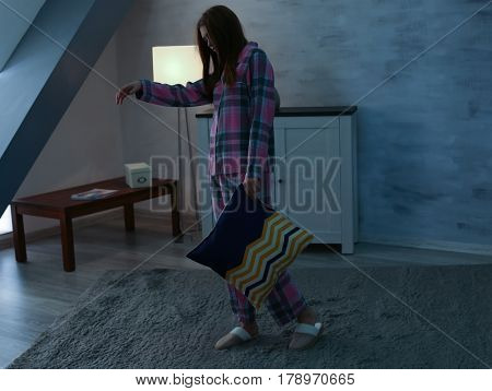 Young sleepy woman with pillow suffering from somnambulism at home