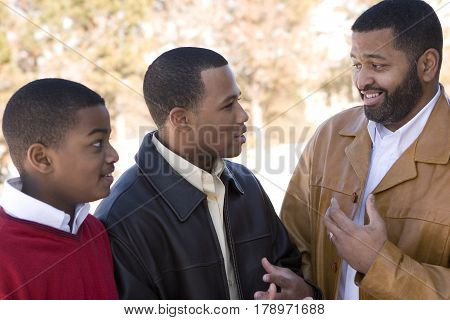 Happy African American father and his teenage sons.