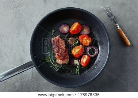Delicious steak with aromatic rosemary, tomatoes and onion in grill pan on grey table