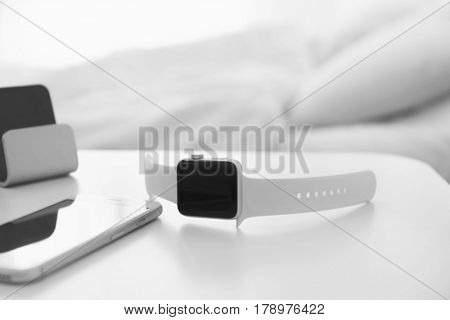 Sleep tracker and mobile phone on table in bedroom