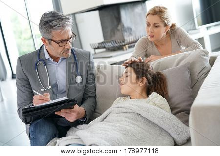 Doctor visiting sick little girl at her house