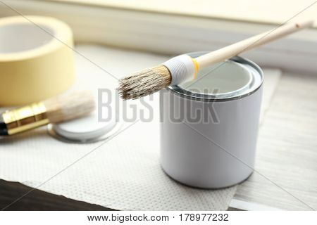 Can with paint and brush on window sill