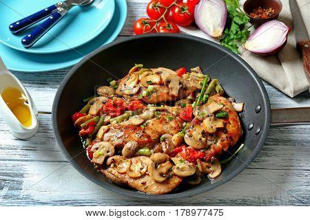 Tasty chicken marsala on pan on table