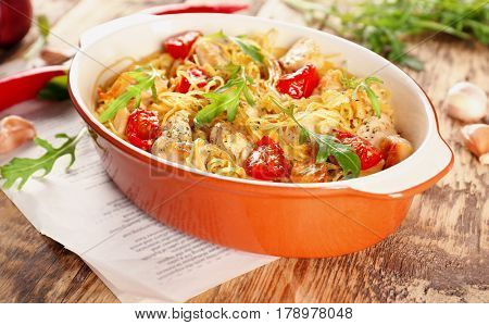 Baking dish with delicious chicken spaghetti on table
