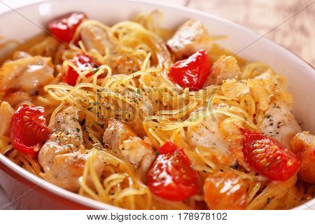 Delicious spaghetti with chicken and tomatoes in baking dish