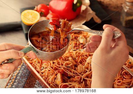 Woman adding sauce to chicken spaghetti in baking dish