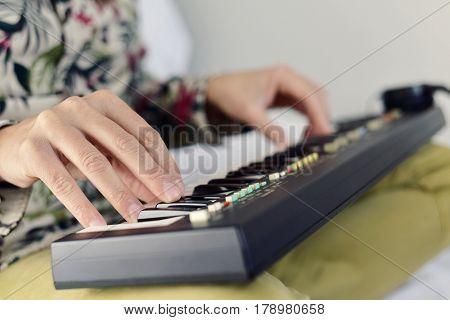 closeup of a young caucasian man playing a portable electronic keyboard