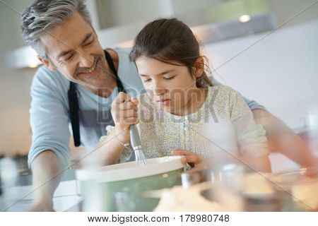 Daddy with daughter baking cake together in home kitchen