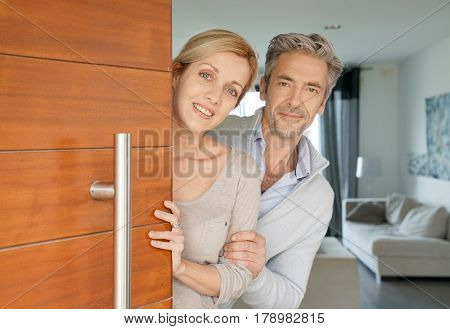 Couple opening house front door to welcome people in