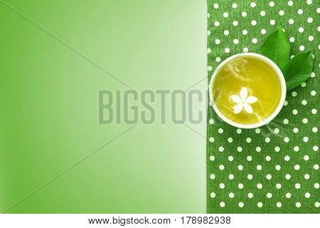 Top view shot of a hot cup of tea with green leaf decoration with green napkin on green background Organic green Tea ceremony time concept