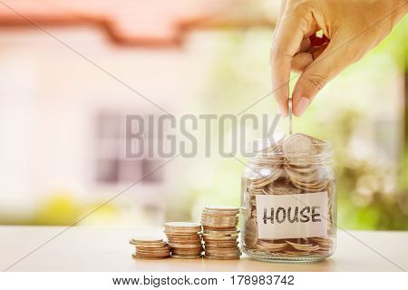 Hand putting Coins in glass jar and HOUSE label with blur of house background for money saving for house or real estate loan concept