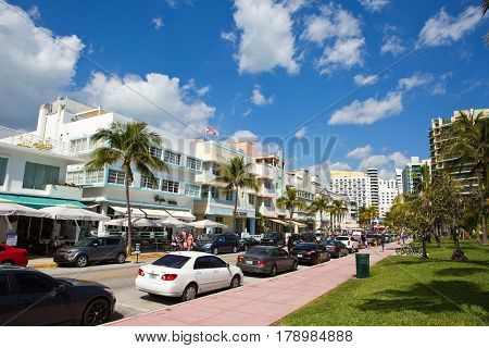 MIAMI BEACH FLORIDA - FEBRUARY 15 2017: Tourists stroll along famous Ocean Drive which runs parallel to Southbeach in Miami Beach Florida USA on February 15 2017.