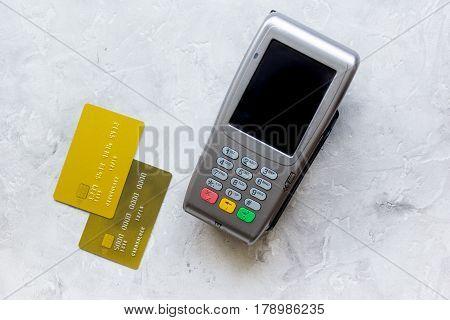 payment terminal with credit card on stone table background top view
