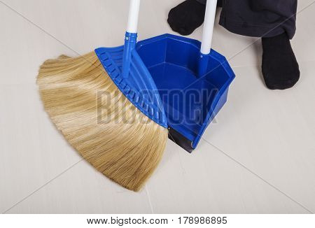 Woman Legs With Broom And Dustpan Sweeping Floor