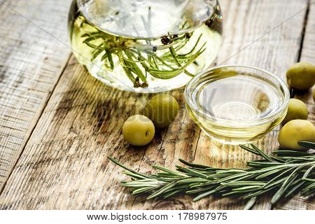 Glass bottle with olive oil and herbs on wooden table background