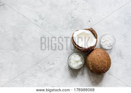 fresh coconut with organic cosmetic oil in glass jar on gray background top view