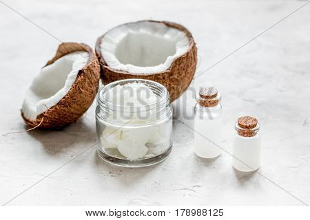 fresh coconut with organic cosmetic oil in glass jar on white background