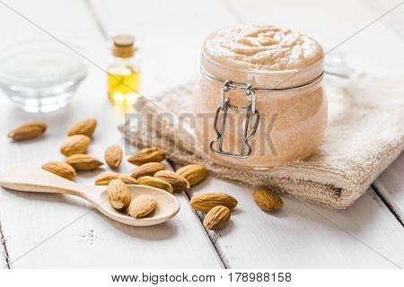 natural scrub with almond oil and white sugar on light table background