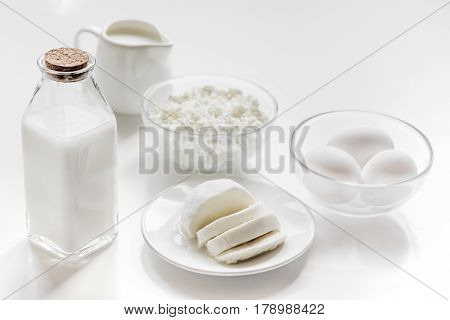 monochrome concept with dairy products for proteic breakfast on white table background
