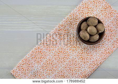 Whole Nutmeg In Bowl With Orange Napkin