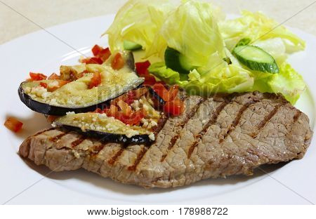 Grilled minute steak slice garnished with sauteed eggplant (aubergine) and chopped tomatoes topped with grated cheese and served with a lettuce and cucumber salad