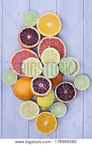 Variety of citrus fruits (orange blood oranges lemons grapefruits and limes) over a blue wood table top rustic background. Image shot from overhead.