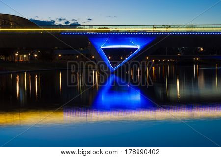 Night time lights on the Adelaide Oval foot bridge and it's reflection on the Torrens river in the CBD of Adelaide in South Australia.