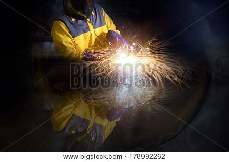 Industrial worker , Electric Grinders metal and many sharp sparks inside piping construction with confined space .