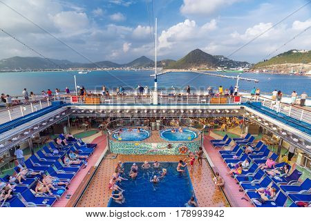 ST MAARTEN CARIBBEAN - SEPTEMBER 22 2013: People rest on the deck of a cruise liner near the St.Maarten island