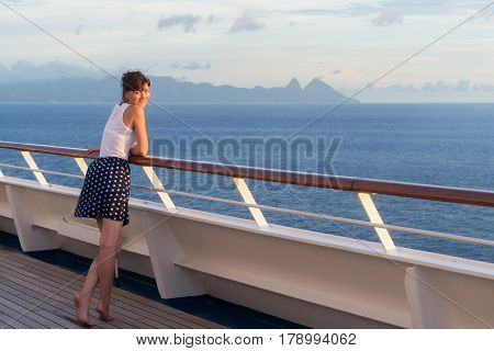 young woman in dress stands on the deck of cruise liner