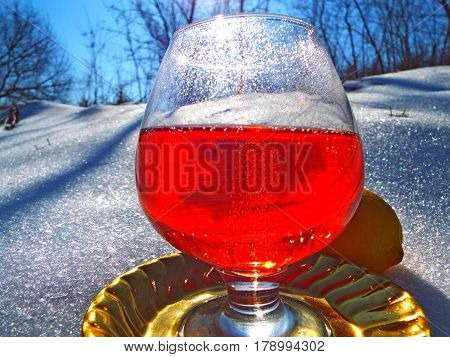 a glass of the mysterious drink on a winter landscape