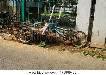 a unique transportation combination from cart and bicycle parked near green fence on side the street photo taken in Jakarta Indonesia java