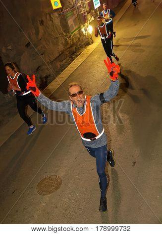 STOCKHOLM SWEDEN - MAR 25 2017: Happy man in reflex vest running in a dark tunnel in the Stockholm Tunnel Run Citybanan 2017. March 25 2017 in Stockholm Sweden