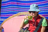 """Lady with sunglasses and hat having a cup of coca leaves tea known as """"Mate de Coca"""" typical hot drink of local people leaving at high altitude on the Andes in Peru and Bolivia. Shot outdoors under a bright sunlight. Square frame. poster"""