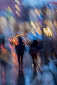 Abstract background of blurred people figures under umbrellas, city street in rainy evening. Light illumination from lanterns and shop windows. Intentional motion blur. Concept of seasons, weather, modern city. poster