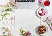 Feminine flat lay workspace with laptop cup of tea macarons and flowers on white wooden table. Top view mock up. poster