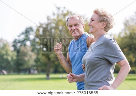 Happy senior man looking at woman while jogging in park
