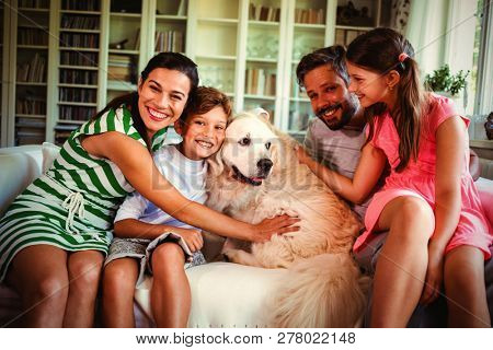 Family with dog sitting on sofa in living room at home